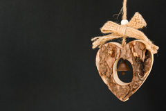 Bark wooden heart on a rope with little opaque brass bell in the Stock Images