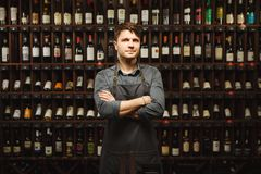Barkeeper stands in wine cellar with shelves full of bottles. Barkeeper in apron stands in wine cellar with large shelves full of closed bottles with exquisite Royalty Free Stock Photo