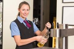 Barkeeper in bar of bar het vullen glas met bier stock fotografie