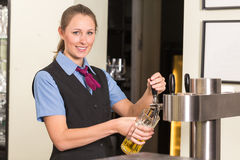 Barkeeper in bar or pub filling glass with beer. Barkeeper in a bar or pub filling glass with beer stock photography