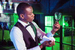 Barkeeper checking a wine glass after cleaning. Barkeeper standing at bar counter and checking a wine glass after cleaning stock photo