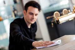 Barkeeper cleaning counter with napkin. Young barkeeper cleaning counter with napkin in bar Stock Photos