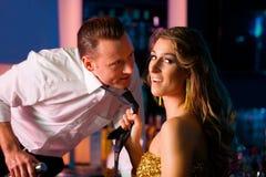 Barkeeper de arrasto da mulher no clube Fotografia de Stock Royalty Free
