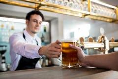 Barkeeper dienend bier aan klant royalty-vrije stock foto