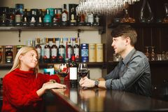 Barkeeper and girl-visitor drink exquisite red wine from glasses. At bar counter with open bottle on it and long wooden shelves full of expensive alcohol drinks royalty free stock photos