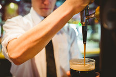 Barkeeper holding beer glass below dispenser tap Royalty Free Stock Images