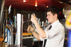 Barkeeper holding glass in front of beer dispenser at bar. Side view of barkeeper holding glass in front of beer dispenser at bar stock photography