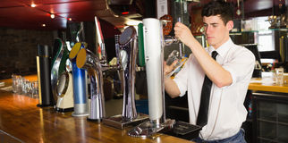 Barkeeper holding glass in front of beer dispenser Royalty Free Stock Images
