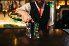Barkeeper pouring alcoholic beverage in glass. Behind restaurant bar counter stock photos