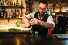 Barkeeper pouring alcoholic beverage in glass. Behind restaurant bar counter Stock Images