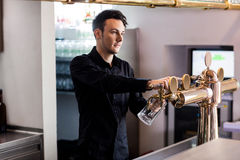 Barkeeper pouring beer in glass from faucet. Handsome barkeeper pouring beer in glass from faucet at bar counter royalty free stock photos