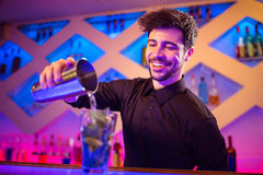 Barkeeper pouring cocktail in glass. Handsome barkeeper pouring cocktail in glass at counter royalty free stock image