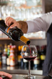 Red wine pouring in glass at bar. Barkeeper pouring red wine in glass on bar in restaurant or hotel stock photography