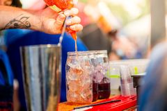 Barkeeper preparing a cocktail. In a plastic glass outdoors. catering royalty free stock photo
