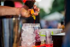 Barkeeper preparing a cocktail. In a plastic glass outdoors. catering royalty free stock images