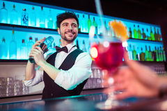 Barkeeper preparing cocktail for customer. At bar counter royalty free stock photography