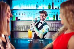Barkeeper preparing cocktail for female customers. Barkeeper smiling while preparing cocktail for female customers at bar counter stock images