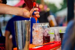 Barkeeper preparing a cocktail. In a plastic glass outdoors. catering royalty free stock photos