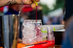 Barkeeper preparing a cocktail. In a plastic glass outdoors. catering stock photo