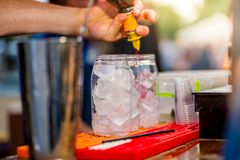 Barkeeper preparing a cocktail. In a plastic glass outdoors. catering royalty free stock image