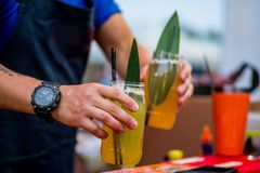 Barkeeper preparing a cocktail. In a plastic glass outdoors. catering stock photos