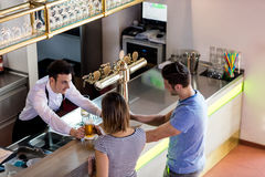 Barkeeper serving beer to couple. High angle view of barkeeper serving beer to couple in bar royalty free stock photos