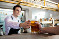 Barkeeper serving beer to customer. Barkeeper serving beer to male customer at restaurant royalty free stock photo