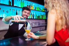 Barkeeper serving cocktail to young woman. Barkeeper serving cocktail to young women at counter in nightclub royalty free stock photography