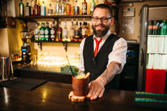 Barkeeper show attractive alcohol cocktail. Barkeeper shows attractive alcoholic cocktail. Handsome alcohol beverage preparation stock photography