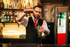 Barkeeper show behind restaurant bar counter. Handsome alcohol beverage preparation stock photo