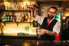 Barkeeper show behind restaurant bar counter. Handsome alcohol beverage preparation royalty free stock images