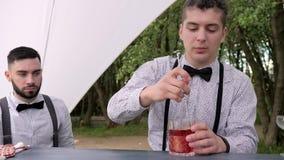 Barkeeperblandningar skedar coctailen för kunden, barmens bak stången, bartendern som gör den kalla drinken i exponeringsglas lager videofilmer