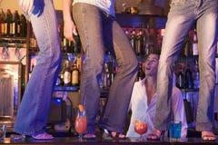Barkellner, der bei drei jungen Frauen tanzen auf Stab den Mund aufsperrt Lizenzfreies Stockfoto