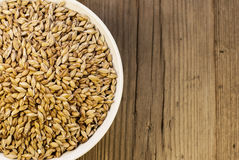 Barley in bowl on wooden background Royalty Free Stock Image