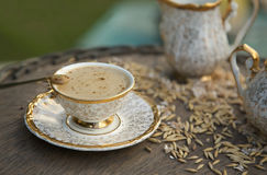 Barley drink. With hot milk in an old destroyed porcelain cup on a wooden surface Stock Photo