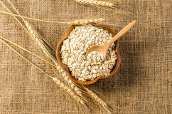 Barley flakes in wooden bowl on sackcloth stock photo