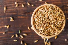 Barley grain in wooden bowl on wooden table Stock Photos