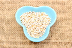 Barley groats in blue bowl on jute canvas Royalty Free Stock Photography