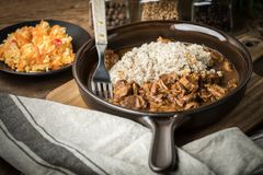 Barley groats with stewed meat. Barley groats with stewed meat served on a pan Stock Photos
