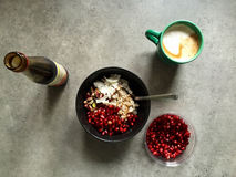 Barley porridge with coconut, pistachios, pomegranate seeds, pomegranate molasses. Top-down shot of breakfast: a black bowl filled with barley porridge (cooked Royalty Free Stock Images