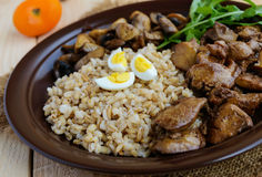 Barley porridge, fried mushrooms and duck liver, boiled quail eggs, tomatoes, arugula - healthy food.  royalty free stock photography