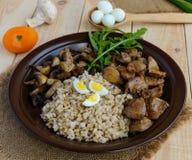 Barley porridge, fried mushrooms and duck liver, boiled quail eggs, tomatoes, arugula - healthy food Stock Photography