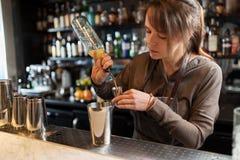Barmaid при шейкер подготавливая коктеиль на баре Стоковая Фотография RF