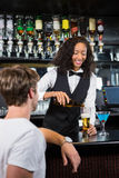 Barmaid pouring beer into beer glass for a man at bar counter Royalty Free Stock Photos