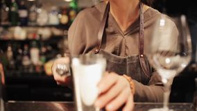 Barmaid preparing cocktail at bar. Alcohol drinks, people and luxury concept - barmaid with glass and shaker preparing cocktail at bar stock footage