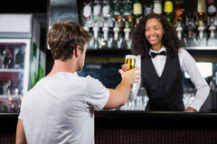 Barmaid serving beer to man Royalty Free Stock Photo