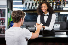 Barmaid serving drink to man Royalty Free Stock Photo