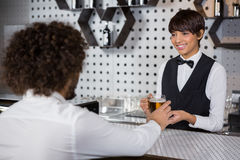 Barmaid serving drink to man Stock Image