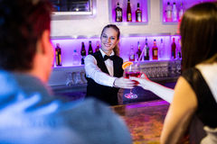Barmaid serving drink to woman Stock Photography