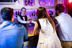 Barmaid serving drink to woman Royalty Free Stock Photo
